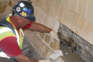 A tile lining being repaired inside a dryer pit